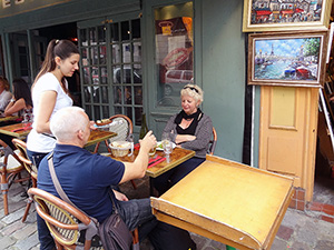 people in a cafe in Montmatre, one of the places to visit on a walking tour of Paris