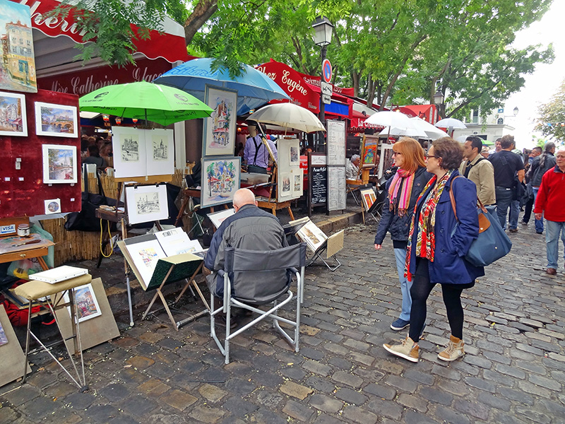 women looking at sidewalk artists on a Paris itineray