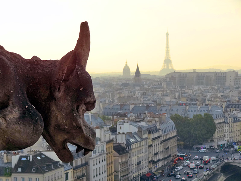 a gargoyle and a view of paris with a map of paris and paris itineraries