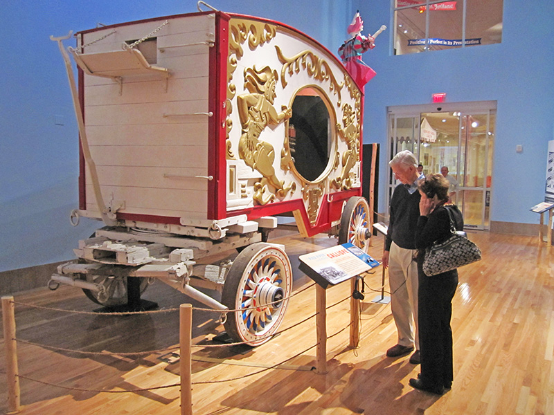 people looking at a cart in a museum - The Ringling Circus Museum - Ringling museum