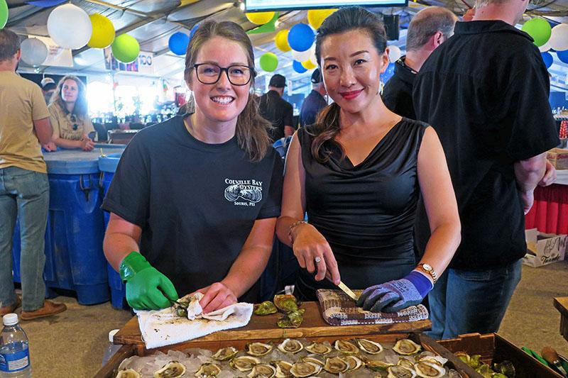 two young women shucking Prince Edward Island oysters near Charlottetown, PEI