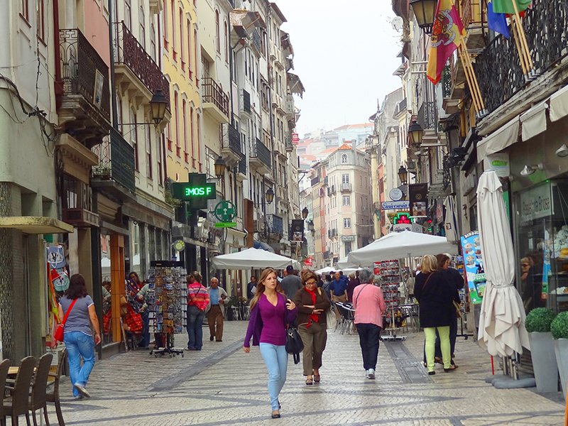 image of people walking on a street illustraing information on the best time to visit Coimbra