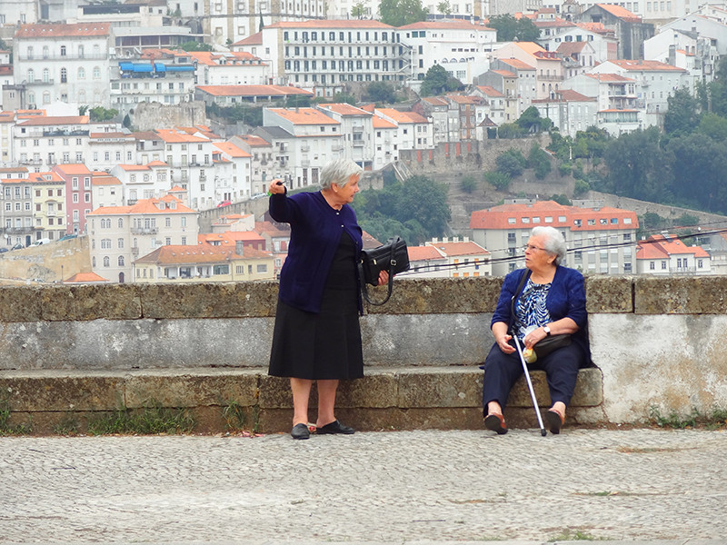 image of two women talking outside a church in Coimbra, Portugal