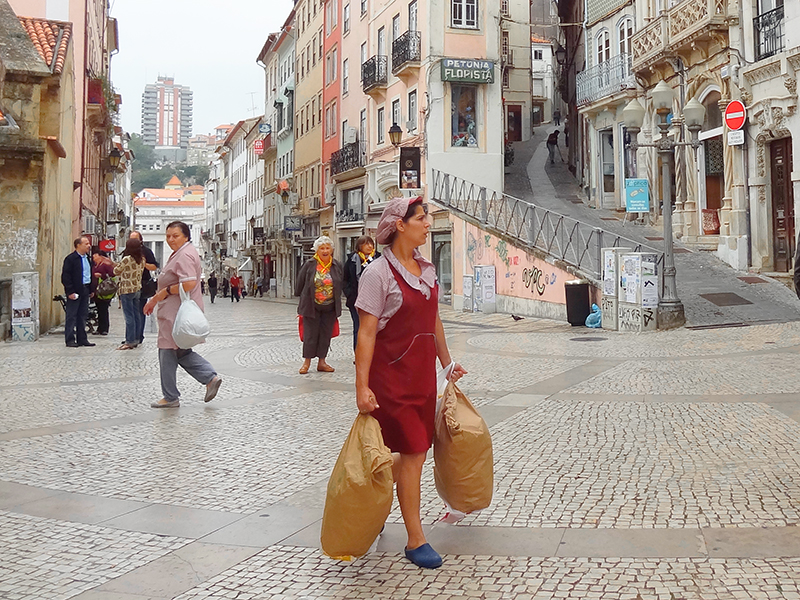 image of a woman walking on a street near the University of Coimbra