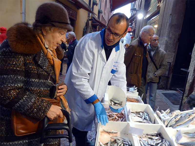 a woman talking with a fishmonger