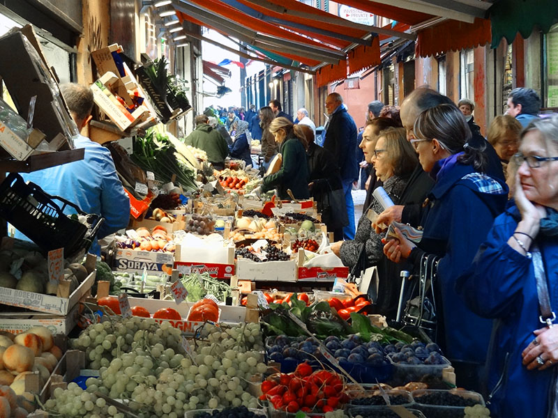 people at vegetable stands in the old market