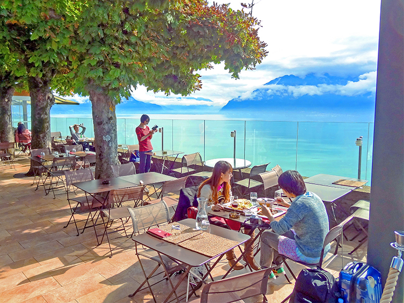 people on the terrace café of Le Baron Tevernier Hôtel looking out upon the Swiss Riviera