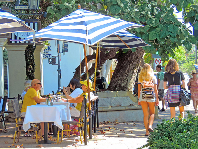people sitting under an umbrella in a cafe in downtown Santa Barbara, the American Rivera