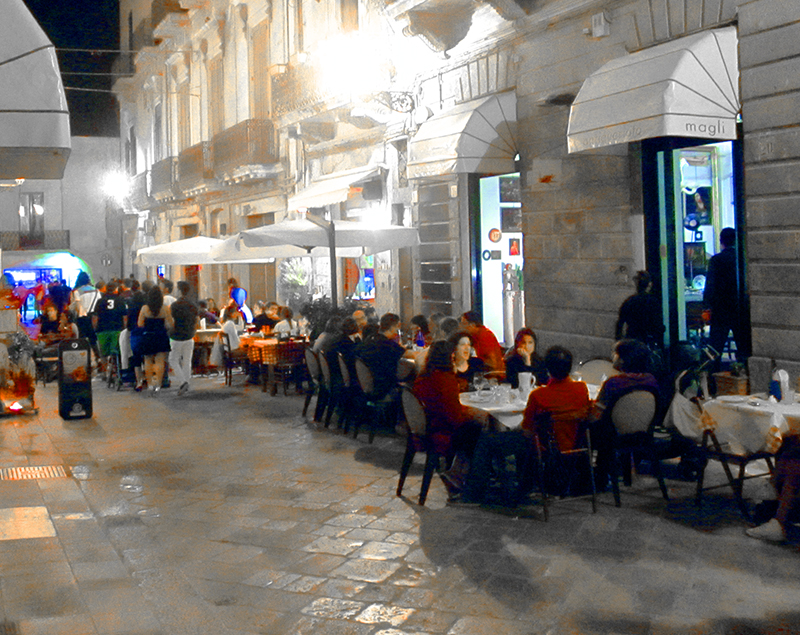 people at outdoor restaurants in Puglia, Italy