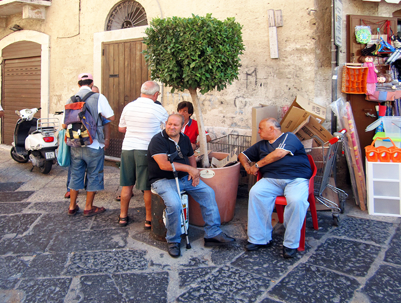 men sitting in chairs on a street in an Italian town