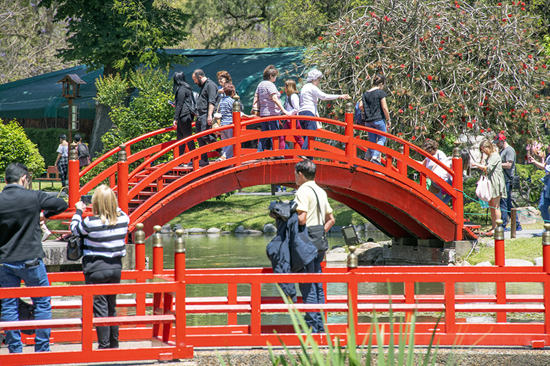people on a red bridge in a garden in palermo, buenos aires