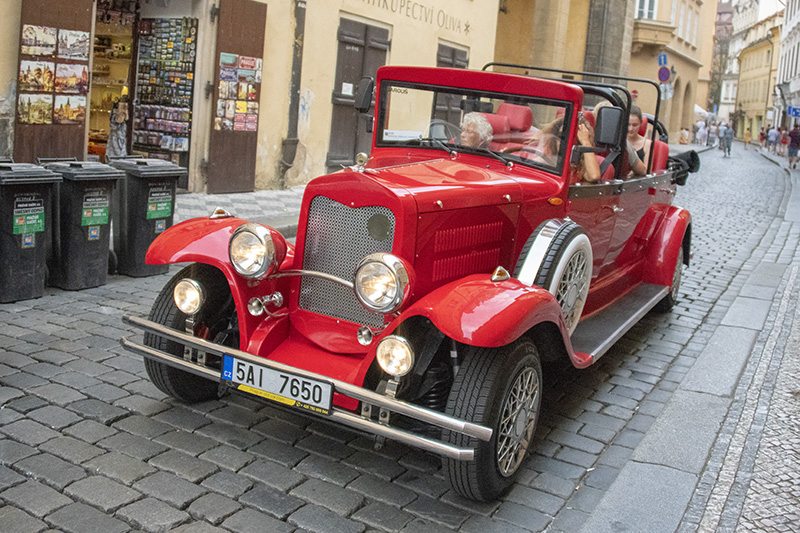 people getting around Prague in a red touring car