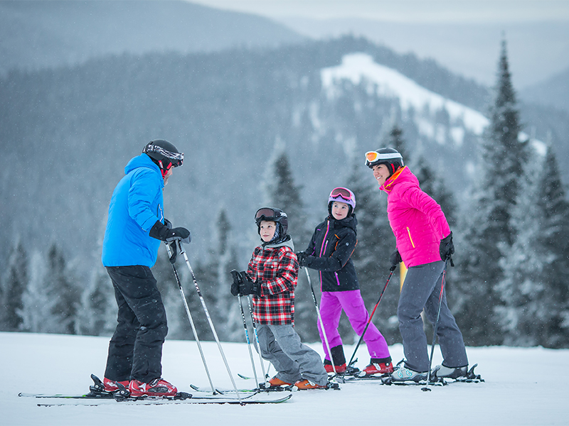 A family skiing above Mount Tremblant village