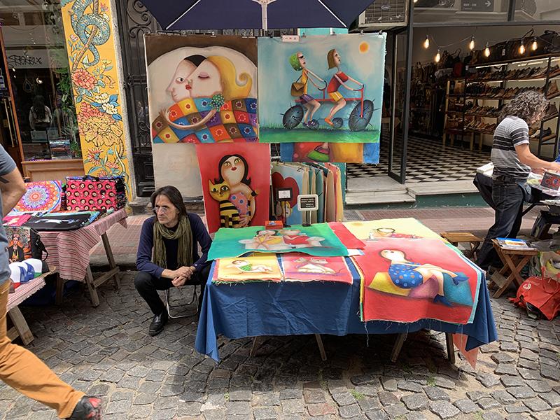 an artist sitting at a table in a street fair
