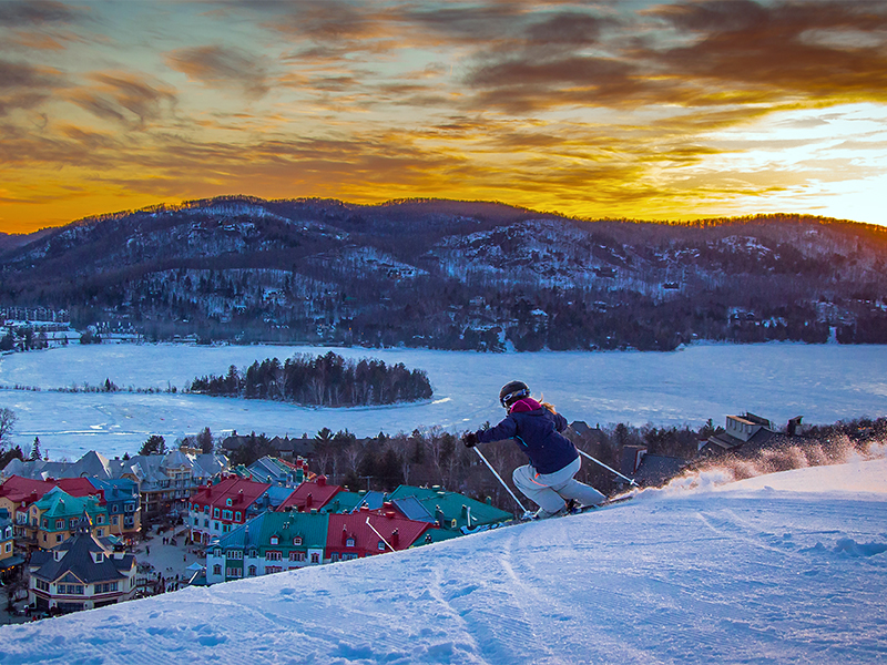 a skier at sunset skiing mount tremblant above mont tremblant village