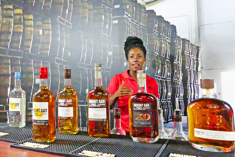 A women showing bottles of Barbados rum