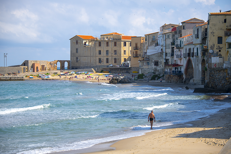 a man walking along the beach in Cefalu, Sicily