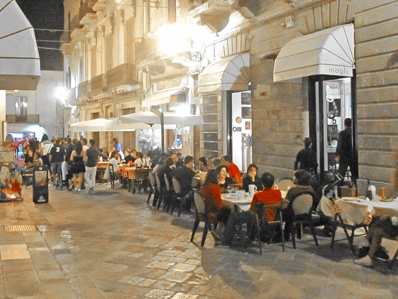 people dining on a pedestrian street in Lecce Italy