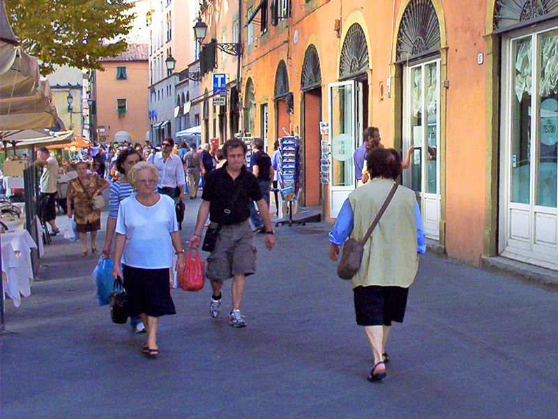 people walking along a colorful street in Lucca Italy
