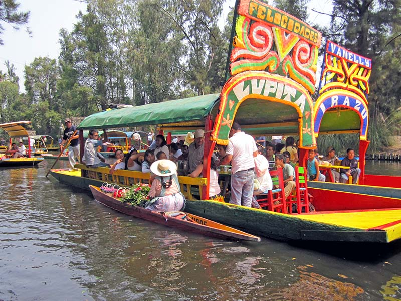 people on colorful boats in Xochimilco, on of the fun things to do in Mexico City