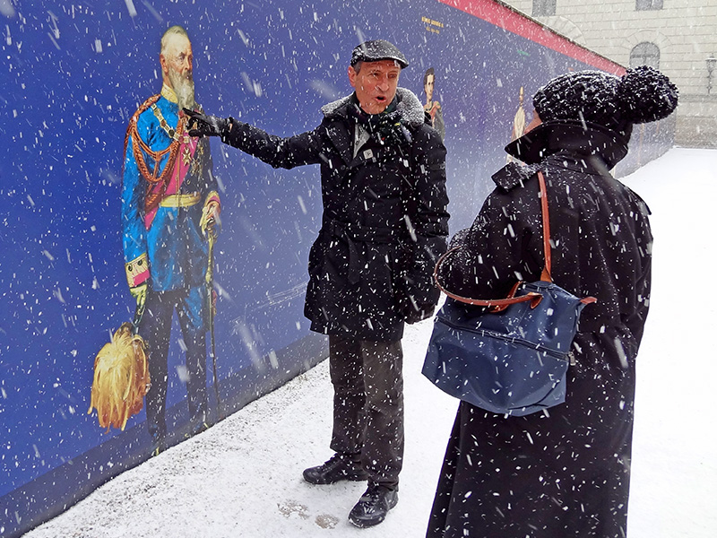 a tour guide pointing to an image of a Bavarian king, whose castle to see on a day trip from Munich to Neuschwanstein