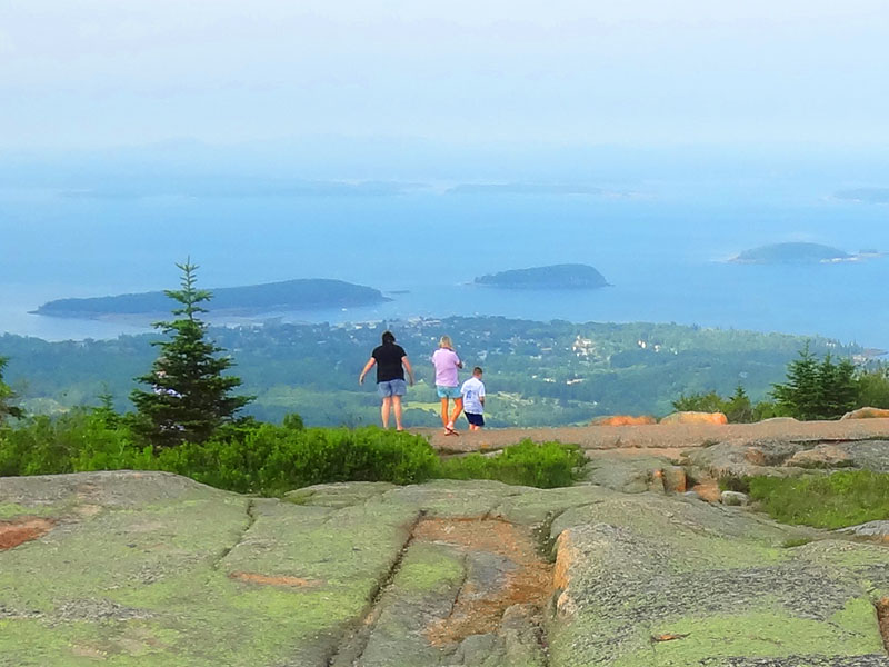 people on a mountain top looking out over the ocean in Acadia National Park, reached near the northern end of Maine Route 1