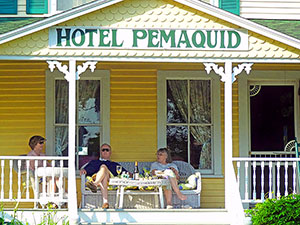 people enjoying coctails on the porch of a hotel on the Maine coast