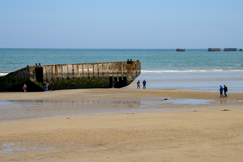 Remnants of the Mulberry Harbors on the beach and in the sea at Arromanches-les-Bains seen on a trip to Normandy from Paris