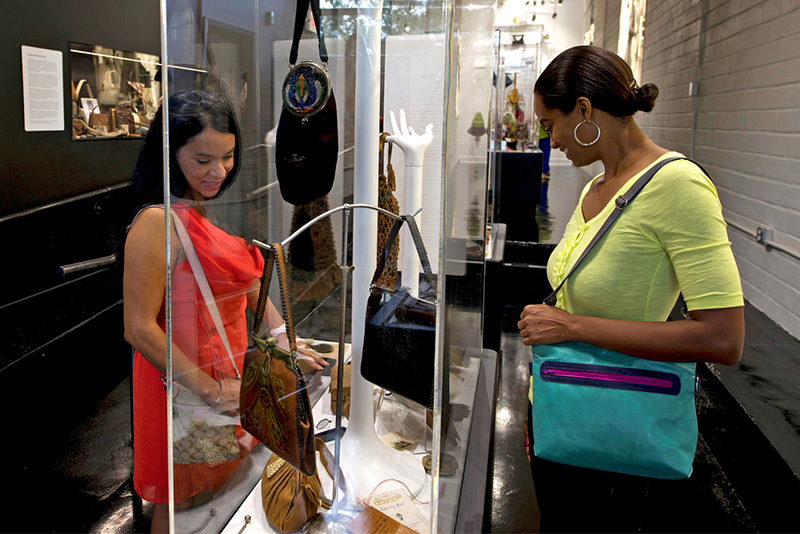 women looking at purses in a museum