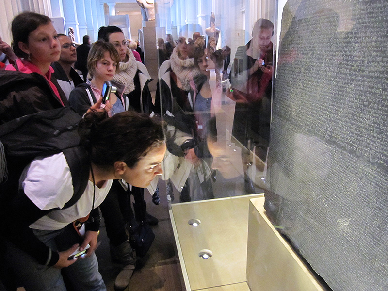 people on a London walking tour looking at the Rosetta Stone in te British Museum