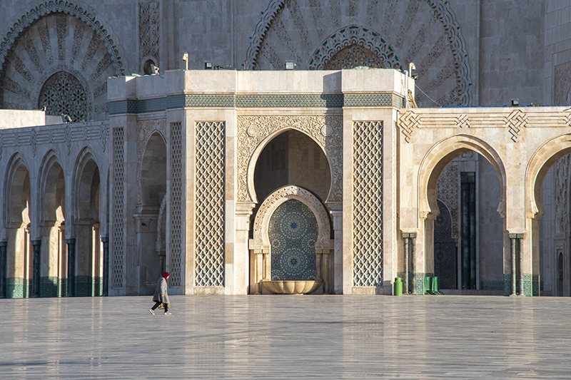 woman walking by a mosque in Casablanca, one of the places to visit in Morocco