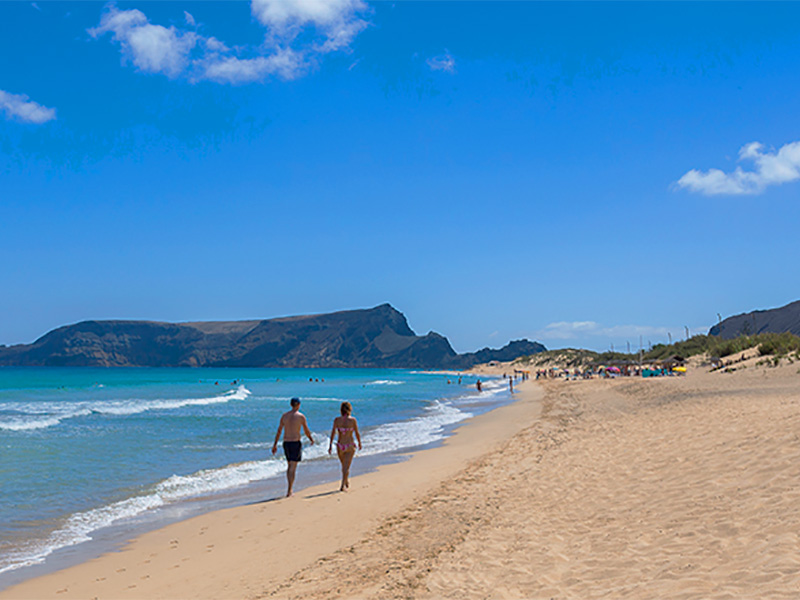 people walking along a beach in Madiera, a good place to recharge your batteries