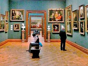 people in a musem looking at paintings