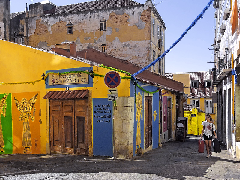 a woman walking along the old streets of Alfama, one of the things to do in Lisbon
