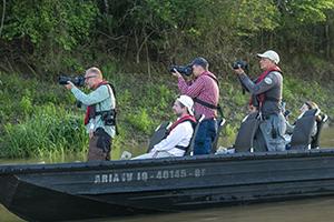 people in a skiff photographing wildlife on an Amazon River cruise in Peru
